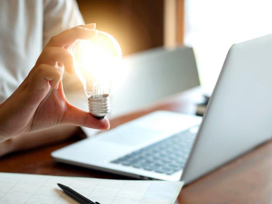 Eine Frau am Laptop mit einer Glühbirne in der Hand.