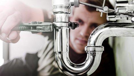 Fallen im Mietvertrag, Mann schraubt Siphon von einer Spüle ab, Foto: iStock.com / lovro77