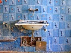 Renovierungskosten, Renovierungsfalle Hauskauf, Wasserleitungen, ein altes Waschbecken mit blauen Fliesen an der Wand, Foto: photo 5000/stock.adobe.com