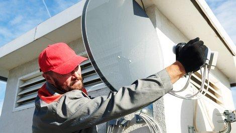Satellitenschüssel, Profi montiert Satellitenschüssel, Foto: Kadmi / stock.adobe.com