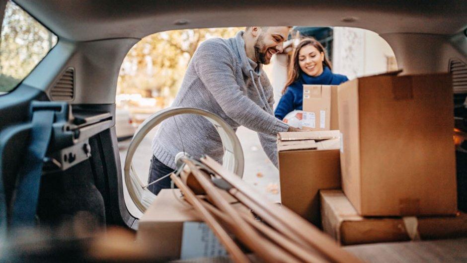 Transportversicherung, junges Paar packt Umzugkartons und Möbel ins Auto, Foto: iStock.com / StefaNikolic