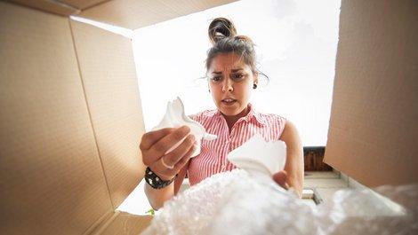 Transportversicherung, Junge Frau schaut in den Karton und hält Scherben in der Hand, Foto: iStock.com / ArtistGNDphotography