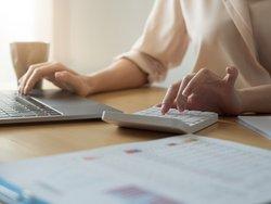 Maximale Darlehenshöhe, Frau sitzt vor Laptop und Taschenrechner, Foto: Natee Meepian / stock.adobe.com