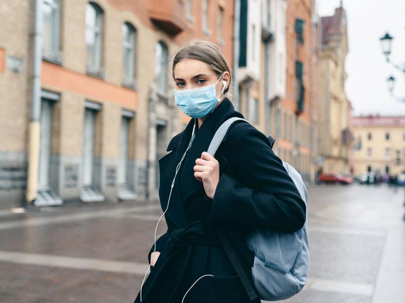 Corona, Eine Frau läuft mit einer medizinischen Maske durch eine Stadt, Foto: ANR Production / stock.adobe.com