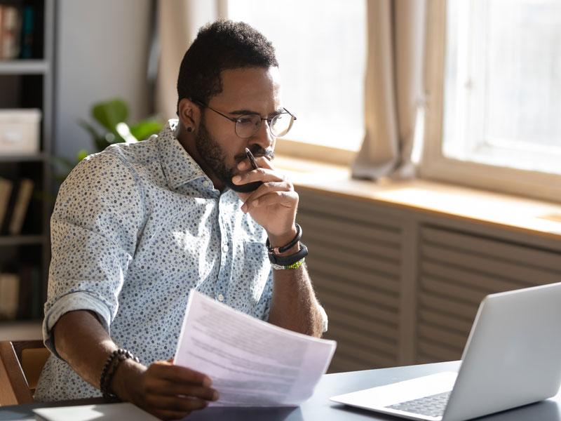 Fallen im Mietvertrag, Mann hat Vertrag in der Hand und schaut kritisch auf einen Laptop, Foto: fizkes / stock.adobe.com