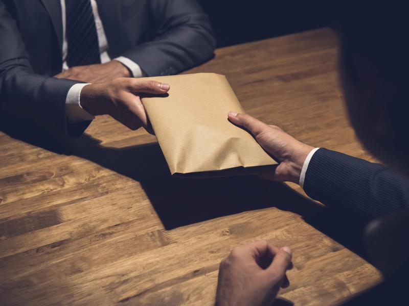 Geldwäschegesetz, Übergabe von einem Umschlag mit Bargeld, Foto: istock.com / Kritchanut