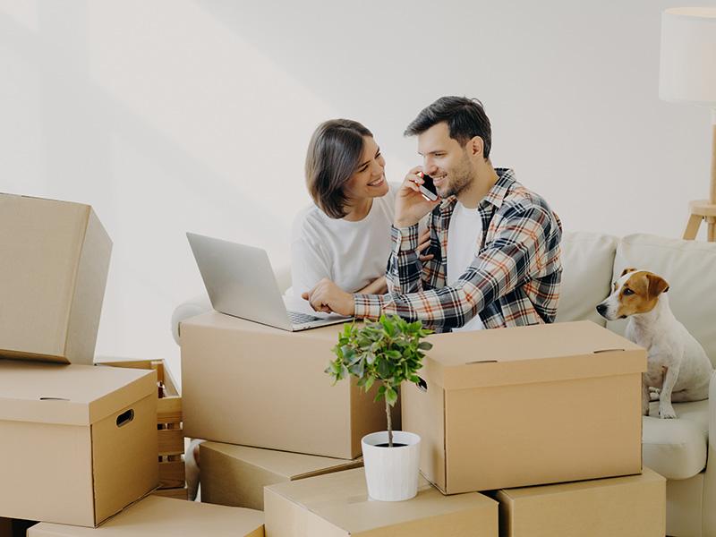 Telefon ummelden, Paar surft in seiner neuen Wohnung im Internet und der Laptop steht auf einem Umzugskarton, Foto: VK Studio / stock.adobe.com